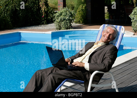 Happy businessman sitting on deck chair with laptop computer next to swimming pool smiling and looking at camera - Stock Photo