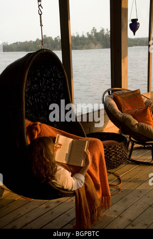 Child relaxing on cottage deck, Lake of the Woods, Ontario, Canada - Stock Photo