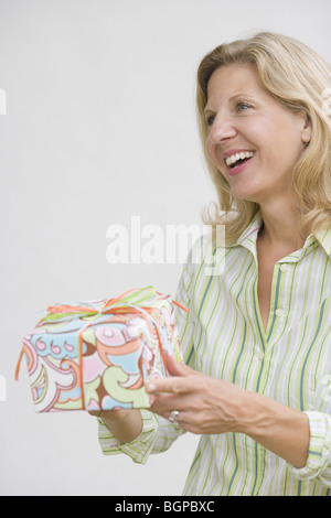 Mature woman holding a gift and smiling - Stock Photo