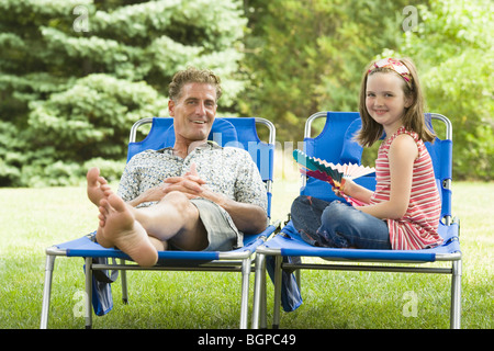 Portrait of a girl sitting on a lounge chair beside her father - Stock Photo