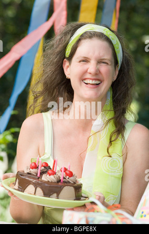 Mature woman holding a birthday cake and smiling - Stock Photo