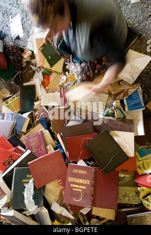 Manual sorting of different types of waste paper before the recycling process - Stock Photo
