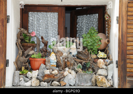Charming window sill decorated with pepples stones flowers window box gnomes Pont St Martin Aosta Valley Italy - Stock Photo