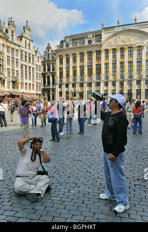 Tourists filming façades of the mediaeval guildhalls at the Grand Place / Grote Markt / Grote Markt, Brussels, Belgium - Stock Photo