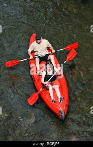 Couple of kayakers kayaking / canoers canoeing in red kayak / canoe on the river Lesse in the Belgian Ardennes, - Stock Photo
