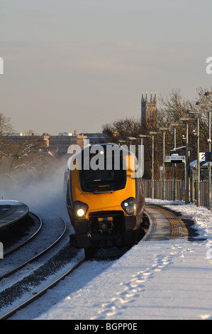 Arriva Cross-Country Voyager train passing through Warwick Parkway station in winter with snow, UK - Stock Photo