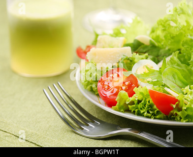 Fresh salad with tomato and quail eggs in a white bowl on a green tablecloth - Stock Photo