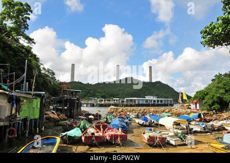 Stilt dwellings of Lamma fisherfolk, looking towards the stacks of Lamma Power Station, Yung Shue Wan, Lamma Island, - Stock Photo