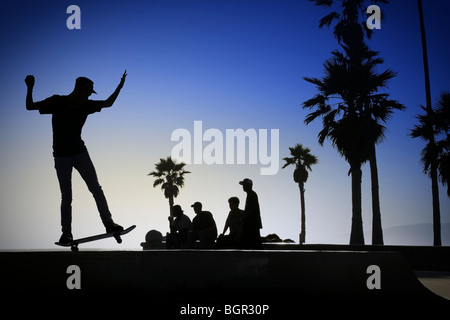 A silhouetted skateboarder manuals accross a low wall on Venice Beach, Los Angeles while his friends watch - Stock Photo