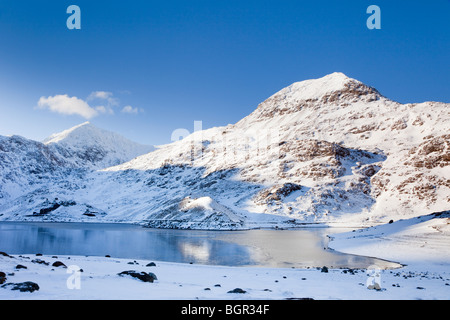 Llyn Llydaw lake with Crib Goch and Mount Snowdon mountain peak with snow in winter from Miners Track in Snowdonia - Stock Photo
