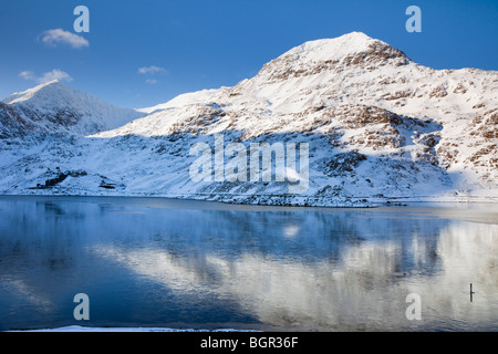 View across Llyn Llydaw (Cronfa Reservoir) to Crib Goch and Mt Snowdon with snow in winter. Snowdonia National Park - Stock Photo