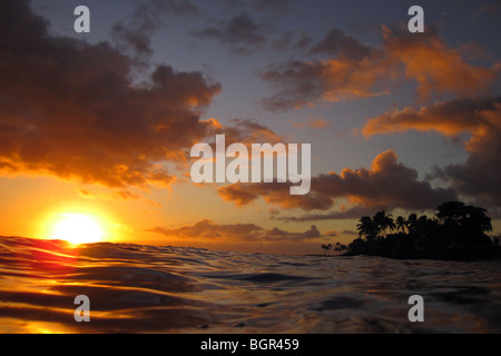 Hawaiian sunset with wave swells, taken from in the water - Stock Photo