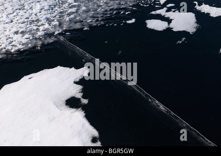 Black ice on a lake with large deep crack and rippled surface and snow drifts - Stock Photo