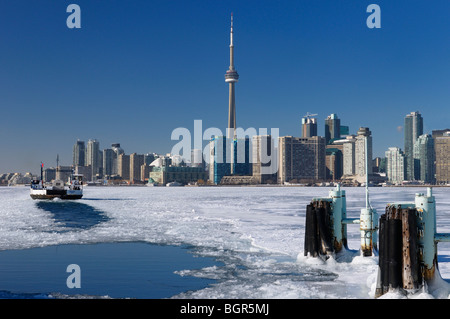 Wards Island Ferry returning to Toronto in winter keeping a channel open on an ice covered Lake Ontario - Stock Photo