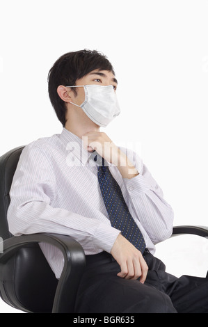 Young man touching throat and wearing surgical mask - Stock Photo