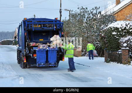 Dustcart lorry and binmen on icy snow covered residential road - Stock Photo