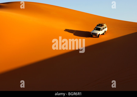 Four-wheel drive car driving at sunset on the pristine slope of a sand dune in the Erg Muzuruq of the Sahara desert, - Stock Photo
