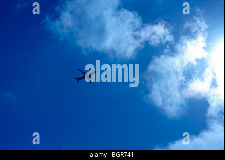Airliner flying into the sun - Stock Photo
