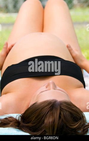 Pregnant woman relaxing outside - Stock Photo
