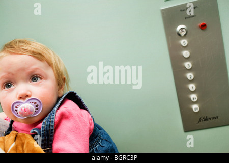A sad baby girl in an elevator, Sweden. - Stock Photo