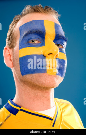 A man with the Swedish flag painted in his face. - Stock Photo