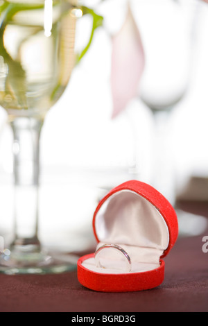 A table laid with a ring in an opened box. - Stock Photo