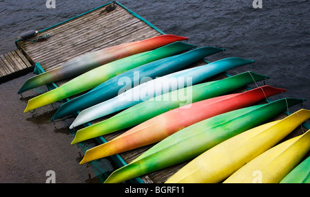 Kayaks in different colors on a jetty, Sweden. - Stock Photo