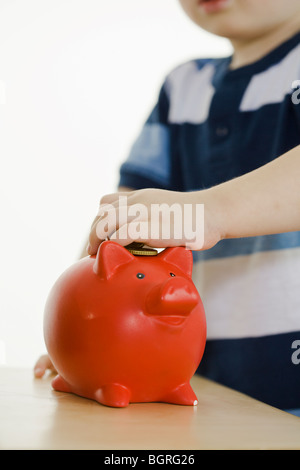 Little boy with pig banks. - Stock Photo