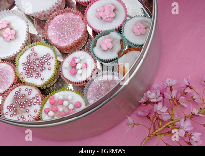 Silver cake tin with decorated fairy cakes on pink background with cherry blossom - Stock Photo