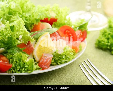 Fresh salad with tomatoes and salmon in a white bowl on a green tablecloth - Stock Photo