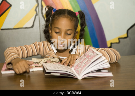 Young girl reads book at an after school community center program in New York CIty. - Stock Photo