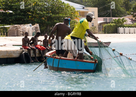 Three men in a Blue Boat: Hauling in a Fishing Net Watched by Boys on a Jetty, Grenada, West Indies. - Stock Photo