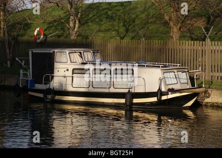 Pleasure cruiser moored at sunset on the River Lea, Tottenham, London, England - Stock Photo