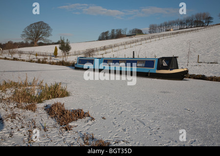 ice bound narrowboats narrow boats on a frozen Lancaster Canal in winter on a cold sunny day - Stock Photo
