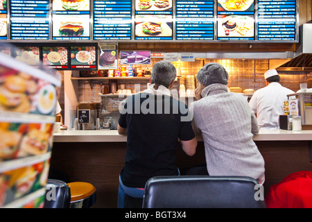 Couple eating in a diner in Manhattan, New York City - Stock Photo