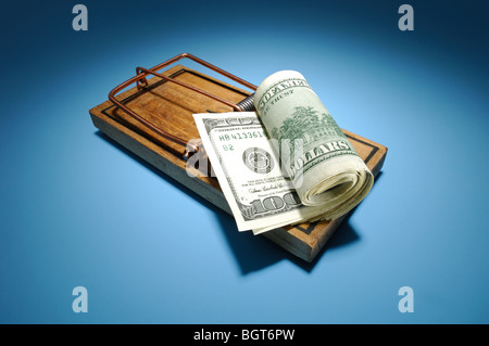 A roll of money sitting on an armed wooden mousetrap