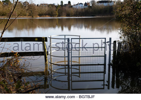 Kissing gate leading to a flooded footpath and field on a Winters day, Sturminster Newton, Dorset England - Stock Photo