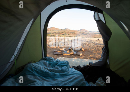 Distant view of camp fire and scene, taken from within a tent, Sesfontein, Kaokoland, Namibia - Stock Photo