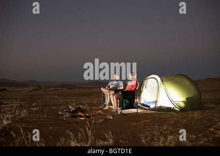 Distant view of couple at campsite in the evening, Sesfontein, Kaokoland, Namibia - Stock Photo
