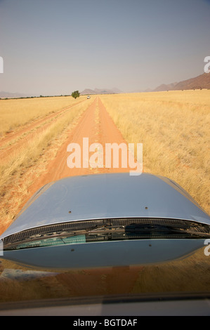 View of sand road ahead taken from inside motor vehicle, Marienflusstal area, Kaokoland, Namibia - Stock Photo