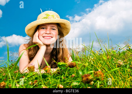 Young teenage girl laying in summer meadow resting chin on hand in straw hat - Stock Photo