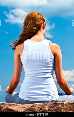 Portrait of young teenage girl practicing yoga outside - Stock Photo