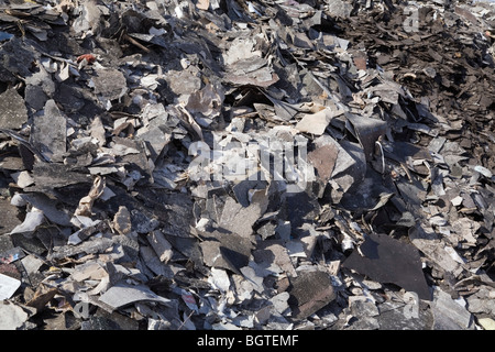 Pile of discarded asphalt roofing shingles in a recycling yard, Laval, Quebec, Canada - Stock Photo