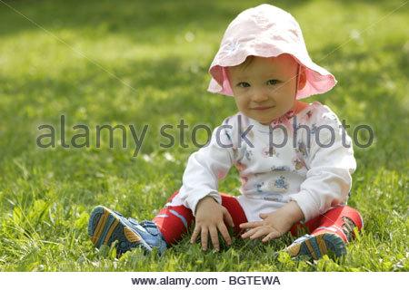 Kleines Maedchen sitzt im Gras - Stock Photo