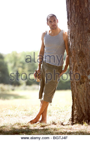 A young man leaning against a tree, holding a beer - Stock Photo