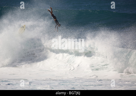 A surfer wipes out on a large wave at Pipleline, Oahu, Hawaii - Stock Photo