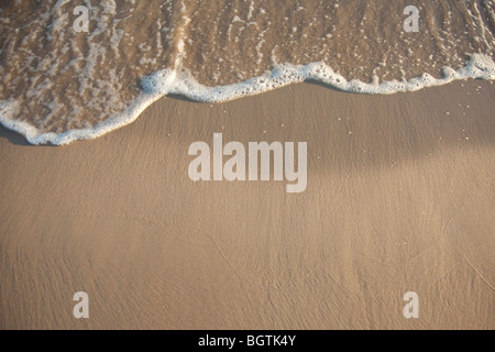 Gentle surf lapping against a golden shore - Stock Photo