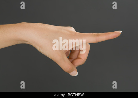 Caucasian female using hand gestures by pointing finger - Stock Photo