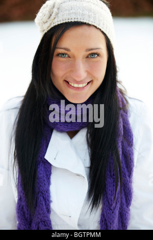 Girl wearing jumper and scarf in winter conditions - Stock Photo