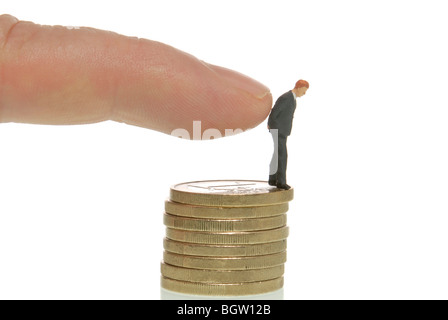 Man's hand pushing a miniature businessman figure from a stack of coins, symbolic image for dismissal - Stock Photo